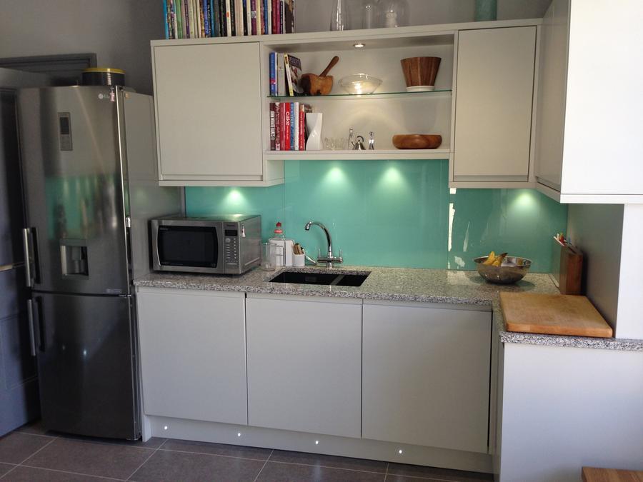 Satin light grey handless kitchen with mint green splashbackn